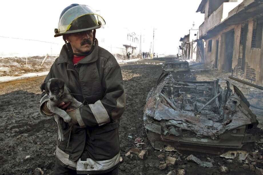 A firefighter carries a puppy after an oil pipeline explosion in the town of San Martin Texmelucan, Mexico, Sunday Dec. 19, 2010.  An oil pipeline operated by Mexico's state-owned oil company Petroleos Mexicanos, or Pemex, exploded  when thieves were attempting to steal oil, killing at least 27 people, injuring at least 52 people and scorching more than 115 homes, authorities said. Photo: Rodolfo Perez, AP