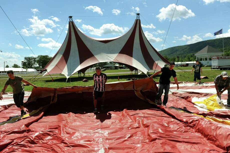 Circus Hollywood workers roll out one side of a circus tent on Saturday, Aug. 10, 2013, at the Altamont Fairgrounds in Altamont, N.Y. The fair opens Tuesday and runs through Sunday. (Cindy Schultz / Times Union) Photo: Cindy Schultz / 00023175A