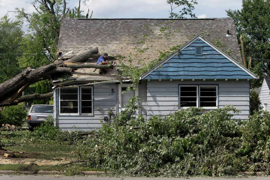 Nick Garvey of Appleton cuts down a tree that damaged the home of his friend Nick Bain at 203 E. Main Street Thursday, Aug. 8, 2013, in Hortonville, Wis. Photo: AP