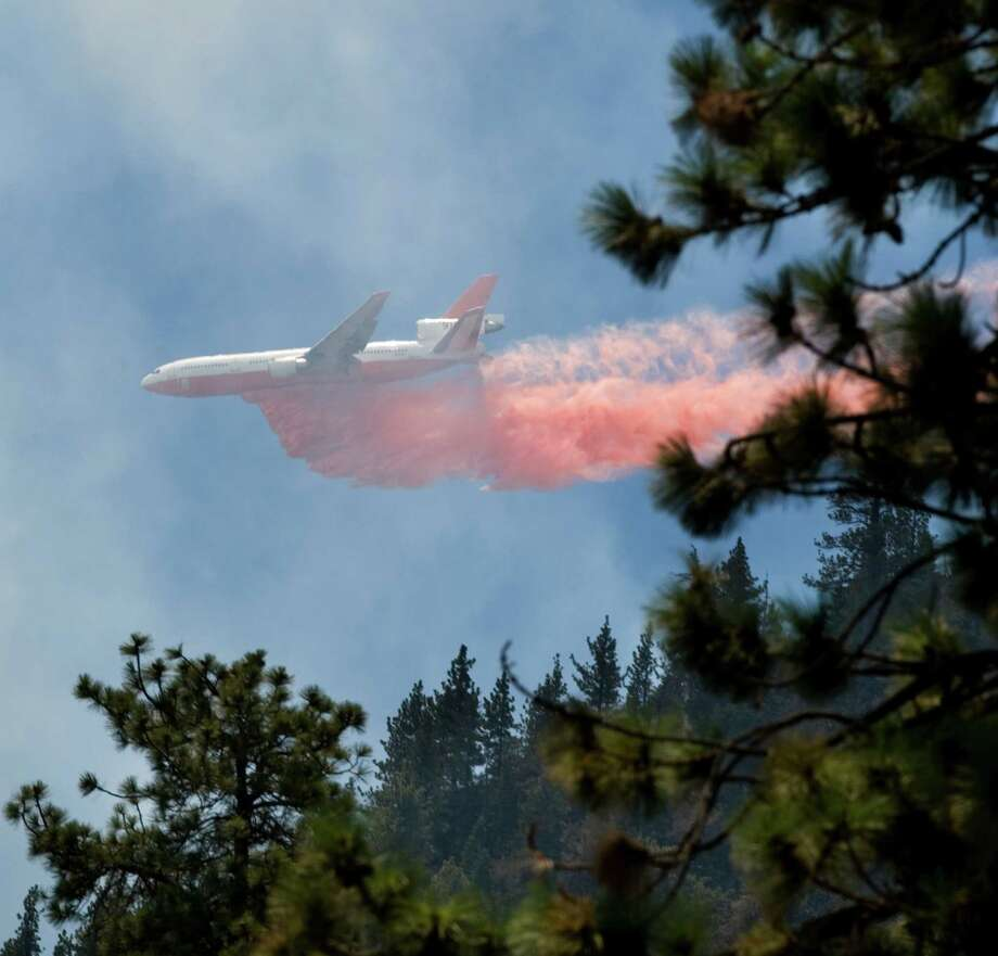 Tanker 911, operated by 10 Tanker Air Carrier drops retardant over the Sharp Fire, Friday, Aug. 9, 2013 in Wrigthwood Calif. A rapidly spreading wildfire chewed through a rugged Southern California mountain range, destroying more than two dozen homes, threatening more than 500 other residences and forcing some 1,800 people to flee. Photo: AP