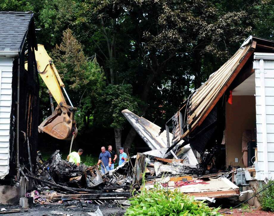 Officials inspect the debris on Saturday, Aug. 10, 2013 after a small plane, piloted by Bill Henningsgaard, crashed into two homes Friday in East Haven, Conn. Four people were killed in the incident. Photo: AP