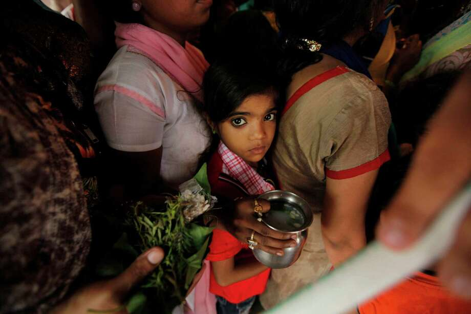 """Indian Hindu devotees queue up to offer prayers at the Nag Vasuki Temple during the annual """"Nag Panchami"""" festival, in Allahabad, India, Sunday, Aug. 11, 2013. The festival is dedicated to the worship of snakes. Photo: AP"""