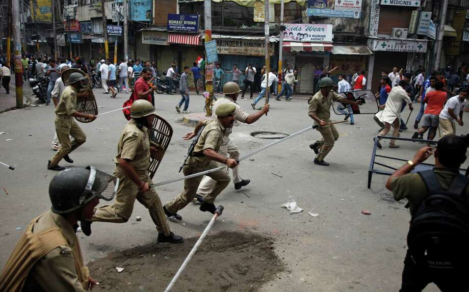 Indian policemen chase Hindus protesting against the state government after rival communities clashed in Kishtwar, in Jammu, India, Saturday, Aug. 10,2013. Indian forces fired warning shots Saturday to enforce a curfew and to push angry people back into their homes in Kishtwar, in the Indian portion of Kashmir where clashes between Muslims and Hindus during Eid celebrations killed at least two people and injured another 24. Photo: AP