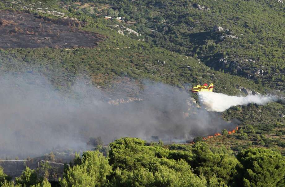 A firefighting airplane drops water over a burning forest in Varibobi, a northwestern suburb of Athens, Tuesday, Aug. 6, 2013. A large wildfire raged through the suburb burning about four homes. No injuries have been reported as the fire spread quickly late night because of strong winds. Photo: AP