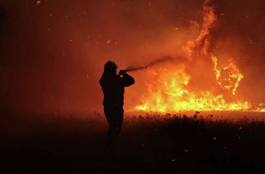 A firefighter works to extinguish a forest fire in Varibobi, a northwestern suburb of Athens, Tuesday, Aug. 6, 2013. A large wildfire raged through the suburb burning about four houses. No injuries were reported. Photo: AP
