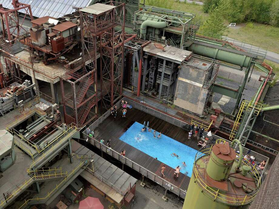 Children enjoy a hot summer day in a factory pool at the former coking plant Zollverein in Essen, Germany, Tuesday, Aug. 6, 2013. The historic former industrial complex was shut down in 1993 and is listed as a UNESCO world heritage site. Photo: AP