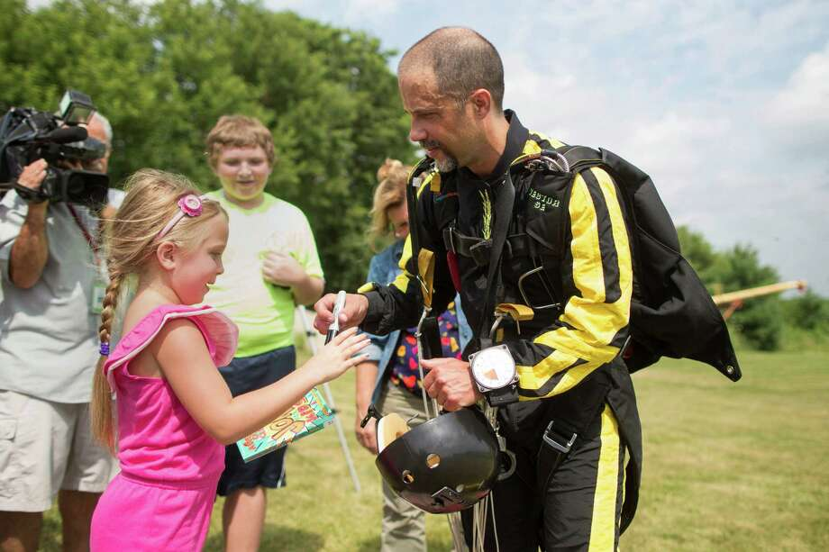 Escape artist Anthony Martin signs an autograph for a girl after successfully escaping from handcuffs and a box he was locked in after being dropped from an airplane in Ottawa, Ill., Tuesday, Aug. 6, 2013. Martin, of Sheboygan, Wis., is no stranger to extracting himself from tricky situations. Since his first escape from handcuffs at the age of 10, he has wriggled his way out of straitjackets, ropes, chains, jail cells, coffins and a cage submerged under water. Photo: AP