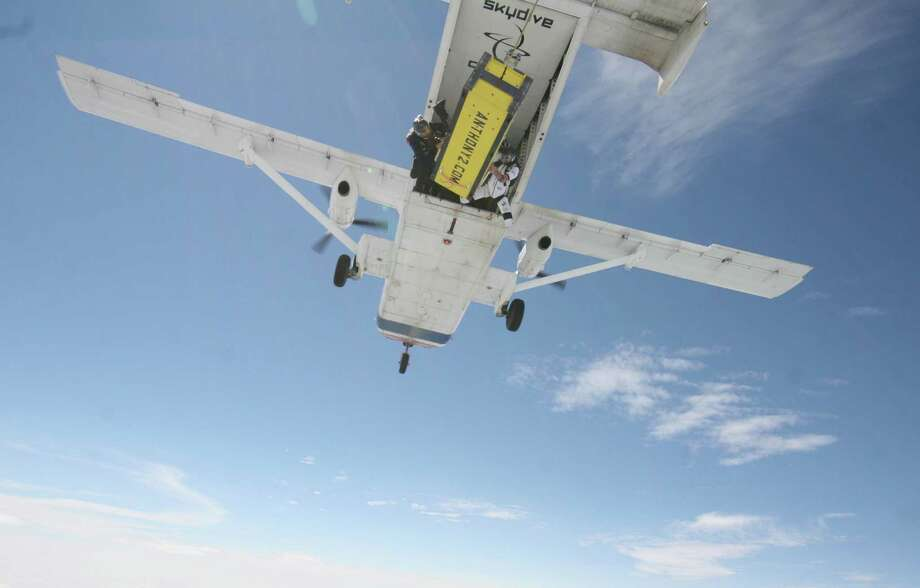 A photo provided by Skydive Chicago shows escape artist Anthony Martin being dropped out of an airplane while being handcuffed and locked inside a box in Ottawa, Ill., Tuesday, Aug. 6, 2013. Photo: AP
