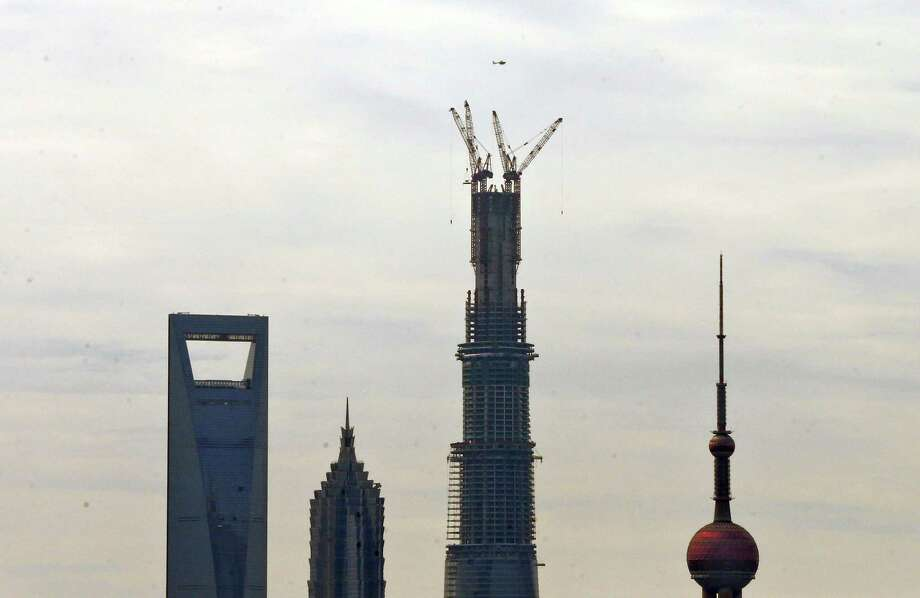 In this photo taken Saturday, Aug. 3, 2013, a helicopter flies past the almost completed Shanghai Tower while a final beam is being raised during a ceremony to mark the structural height of 580 meters (1, 902) with 125 floors in Shanghai, China. According to Chinese media, the Shanghai Tower in the city's Pudong district will eventually reach a height of  632 meters (2,073 feet) when completed next year. Other buildings shown are the Oriental Pearl Tower at right, Jin Mao Tower, second from left, and the Shanghai World Financial Center at left. (AP Photo)  Photo: AP