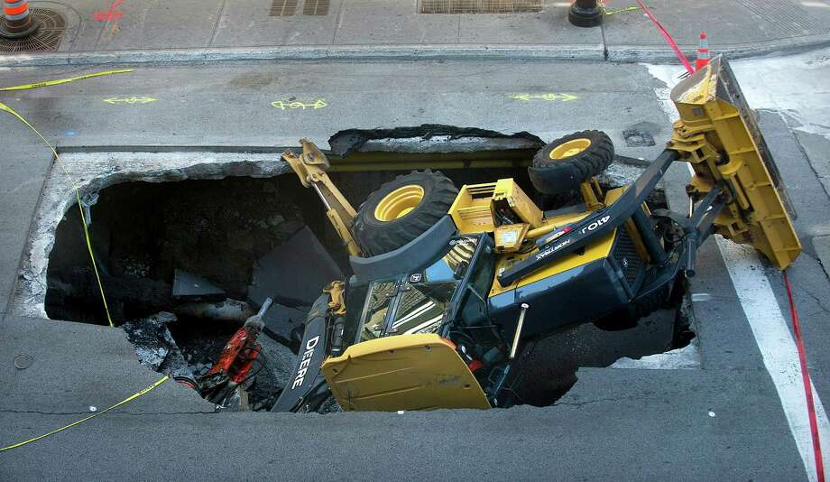 A backhoe is shown on Tuesday, Aug. 6, 2013, after being swallowed by a sinkhole in Montreal .   A Montreal business-owner says city officials ignored his warnings that there was a problem before a a sinkhole swallowed a backhoe. The backhoe had started to chip at asphalt near the corner of Ste-Catherine and Guy streets yesterday when the ground crumbled beneath it and the heavy machine tumbled in. The driver of the backhoe was not injured but was taken to hospital to be checked out as a precaution. Photo: AP