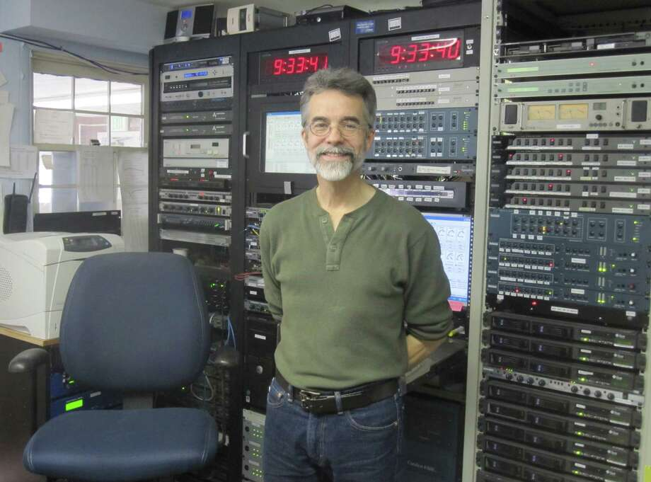 "WSHU program director and ""Morning Edition"" host Tom Kuser stands before a wall of equipment that keeps programs sorted out and on schedule. Photo: Contributed Photo / Fairfield Citizen"