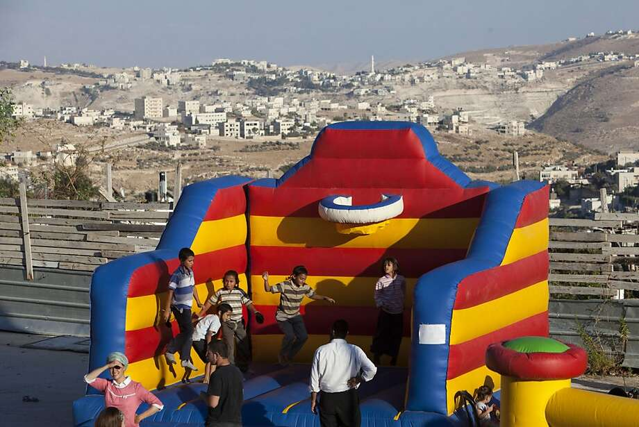 Israeli children play near a construction site during a ceremony to mark the resumption of the building of homes in East Jerusalem under a settlements-for-prisoners deal with Palestinians. Photo: Sebastian Scheiner, Associated Press