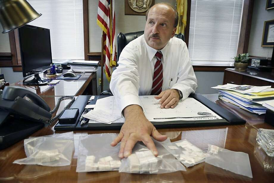 """Joseph Coronato, prosecutor of Ocean County, N.J., displays packets of confiscated heroin as he discusses new approaches to prosecuting drug dealers. """"We're going to be ruthless,"""" he says. Photo: Mel Evans, Associated Press"""