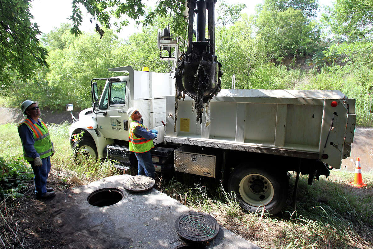 Carlos Martinez (left) and Aaron Loney use a claw mechanism to extract debris as a SAWS maintenance crew cleans out a clogged siphon system near the intersection of Eisenhauer and Corinne on August 7, 2013.
