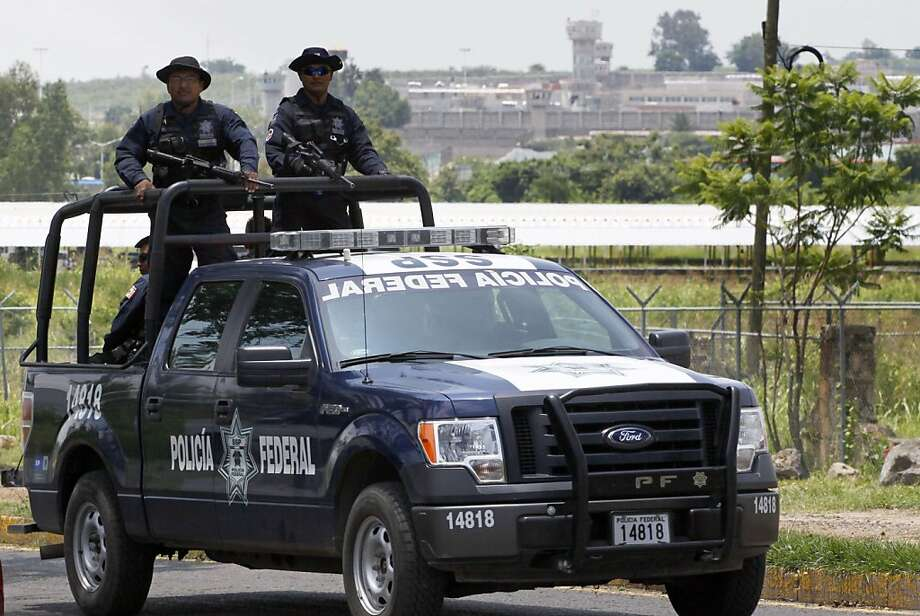 A unit of the Mexican Federal Police patrols the surroundings of the Puente Grande State prison (background) in Zapotlanejo, Jalisco State, Mexico, on 9 August, 2013 where former top Mexican cartel boss Rafael Caro Quintero -- who masterminded the kidnap and murder of a US anti-drug agent in 1985 -- was informed early Friday that a court ordered his release. A criminal court in the western state of Jalisco approved Rafael Caro Quintero's release on August 7, a court official who asked not to be identified told AFP. Caro Quintero has served 28 years in prison for the 1985 murder of US Drug Enforcement Administration special agent Enrique Camarena, who was kidnapped in Guadalajara and tortured and murdered.  AFP PHOTO / HECTOR GUERREROHECTOR GUERRERO/AFP/Getty Images Photo: Hector Guerrero, AFP/Getty Images