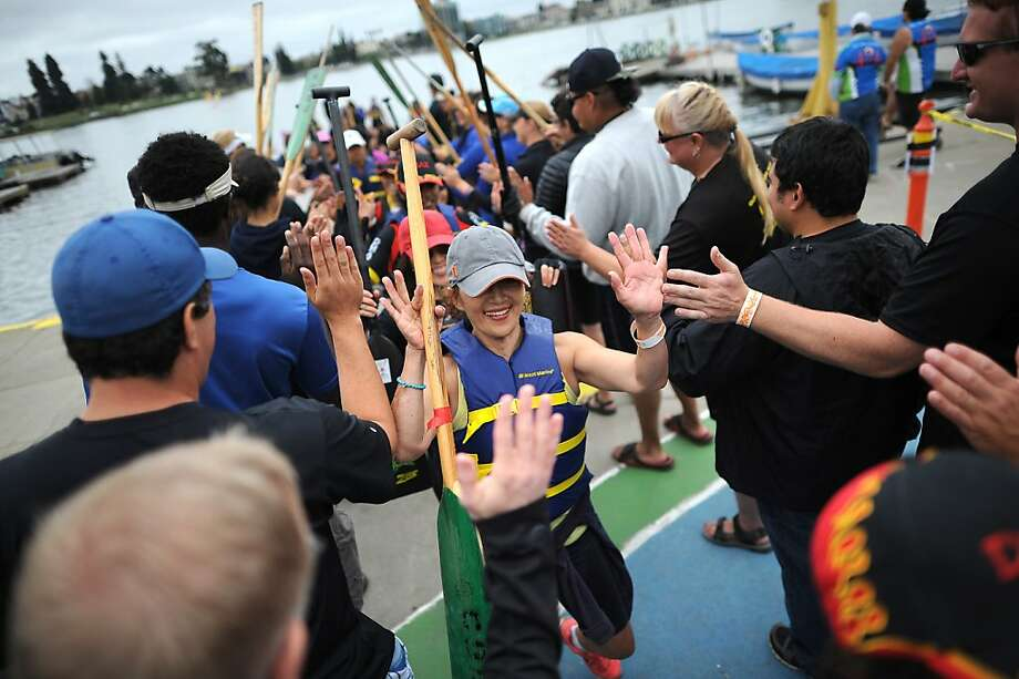 Racers are greeted with high fives by spectators after competing during the Dragon Boat Festival races on Lake Merritt in Oakland. Photo: Michael Short, Special To The Chronicle