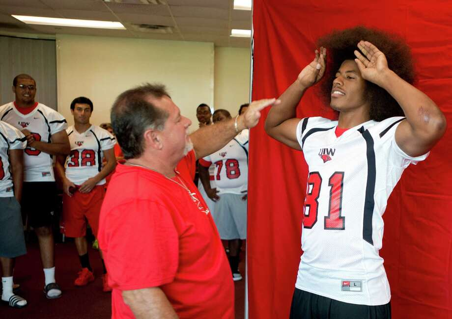 Trey Anderson, right, gets some help taming his hair from photographer Mark Walton, for his team picture during UIW Football picture day, Sunday, August 11, 2013, at UIW Benson Stadium in San Antonio. Read more about the Cardinals' upcoming season on ExpressNews.com. Photo: Darren Abate, Associated Press