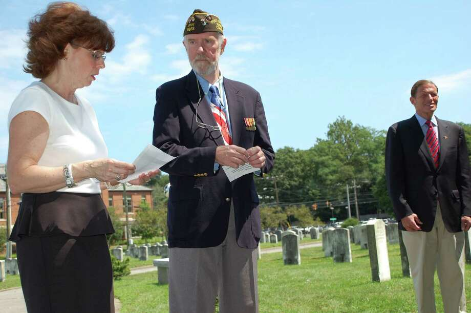 Becky Gallucci, engage life director with Atria Senior Living Darien, left, reads the names of some local World War II veterans, while Phillip Kraft, post commander of the Darien VFW, center, and U.S. Sen. Richard Blumenthal, right, listen. Photo: Jarret Liotta For The Advocate / Stamford Advocate
