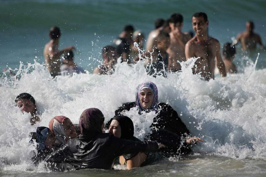 Mostly Palestinians from the West Bank bather in the Mediterranean Sea on the last day of the Eid-al-Fitr holiday, in Tel Aviv, Israel, Sunday, Aug 11, 2013. The three-day Eid al-Fitr holiday marks the end of the holy fasting month of Ramadan. One of the most important holidays in the Muslim world, Eid al-Fitr, is marked with prayers, family reunions and other festivities.  Tens of thousands of Palestinians visit Tel Aviv and other places in Israel after Israel granted travel permits to West Bank Palestinians. Photo: AP