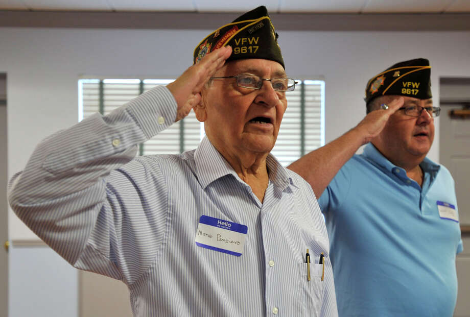 Chaplain Marco Pensiero, left, and Col. Bob Cody lead the room in the Pledge of Allegiance during the Springdale VFW Post 9617 anniversary picnic at the Belltown fire house in Stamford on Sunday, Aug. 11, 2013. Photo: Jason Rearick / Stamford Advocate