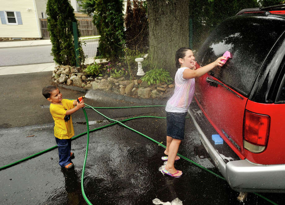 Christopher Astorga, left, sprays his sister, Gabriella, as she scrubs the rear window of their mother's car outside their home in Stamford on Sunday, Aug. 11, 2013. Temperatures in Stamford reached into the 80s. Photo: Jason Rearick / Stamford Advocate