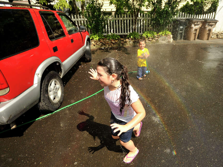 Christopher Astorga sprays his sister, Gabriella, as they wash their mother's car outside their home in Stamford on Sunday, Aug. 11, 2013. Temperatures in Stamford reached into the 80s. Photo: Jason Rearick / Stamford Advocate