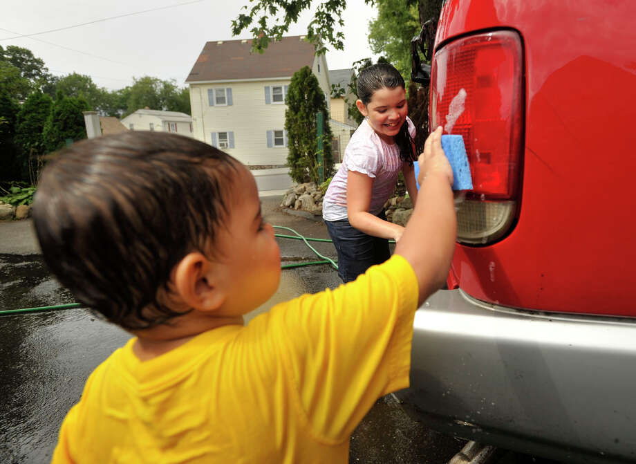 Christopher Astorga, left, and his sister, Gabriella, wash their mother's car outside their home in Stamford on Sunday, Aug. 11, 2013. Temperatures in Stamford reached into the 80s. Photo: Jason Rearick / Stamford Advocate