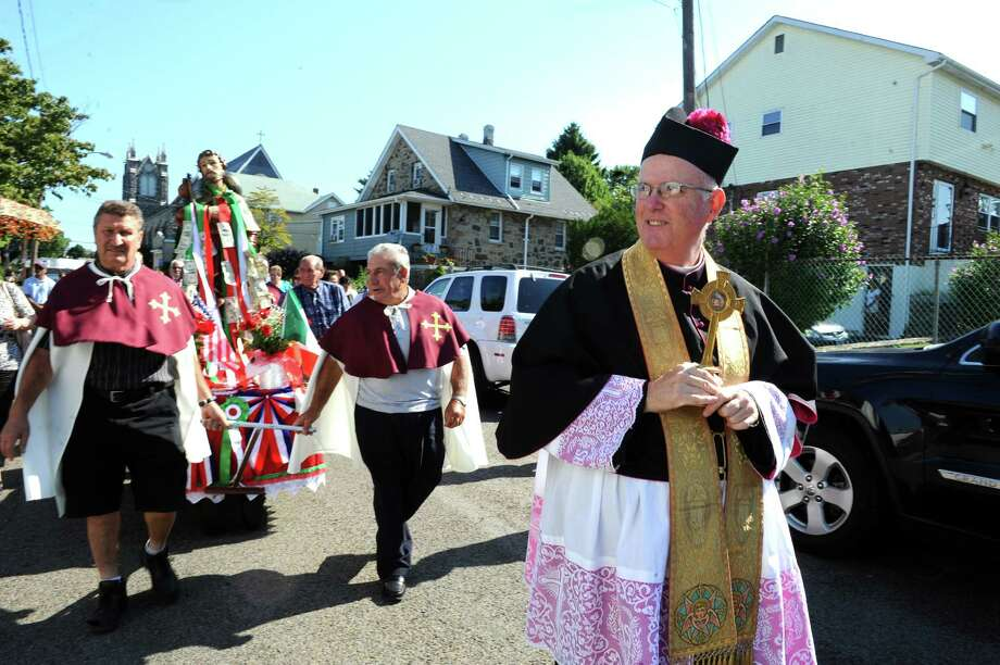 The Reverend  Matthew Rocco Mauriello walks at the annual Saint Roch parade at Chickahominy, in Greenwich, Conn., Sunday, August 11, 2013. Photo: Helen Neafsey / Greenwich Time