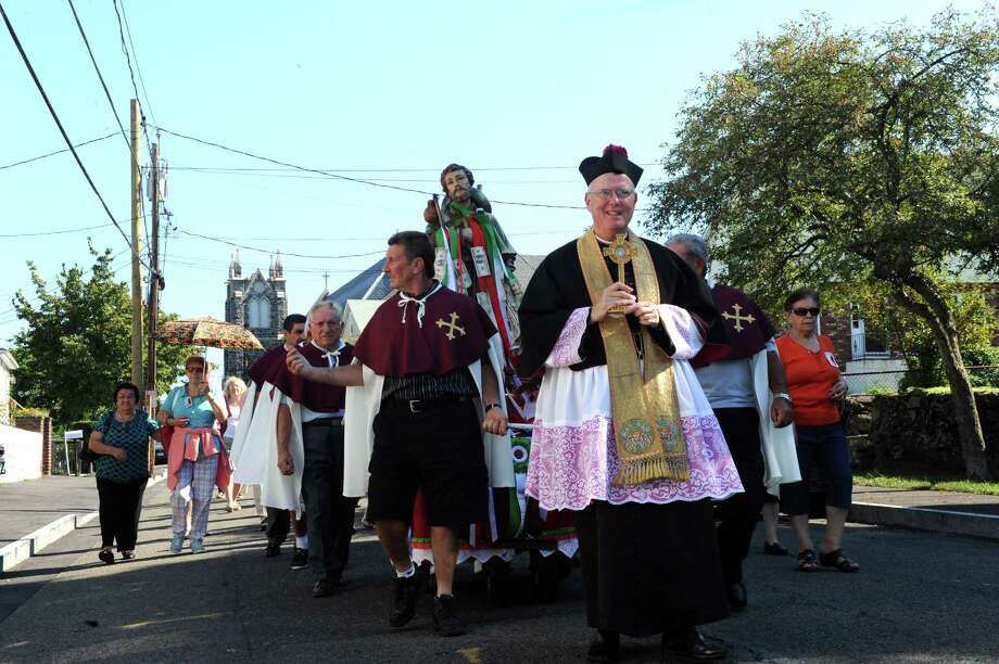 The Reverend  Matthew Rocco Mauriello walk at the annual Saint Roch parade at Chickahominy, in Greenwich, Conn., Sunday, August 11, 2013. Photo: Helen Neafsey / Greenwich Time