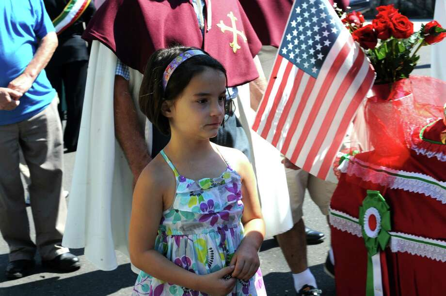 A young girls looks at the annual Saint Roch parade at Chickahominy, in Greenwich, Conn., Sunday, August 11, 2013. Photo: Helen Neafsey / Greenwich Time