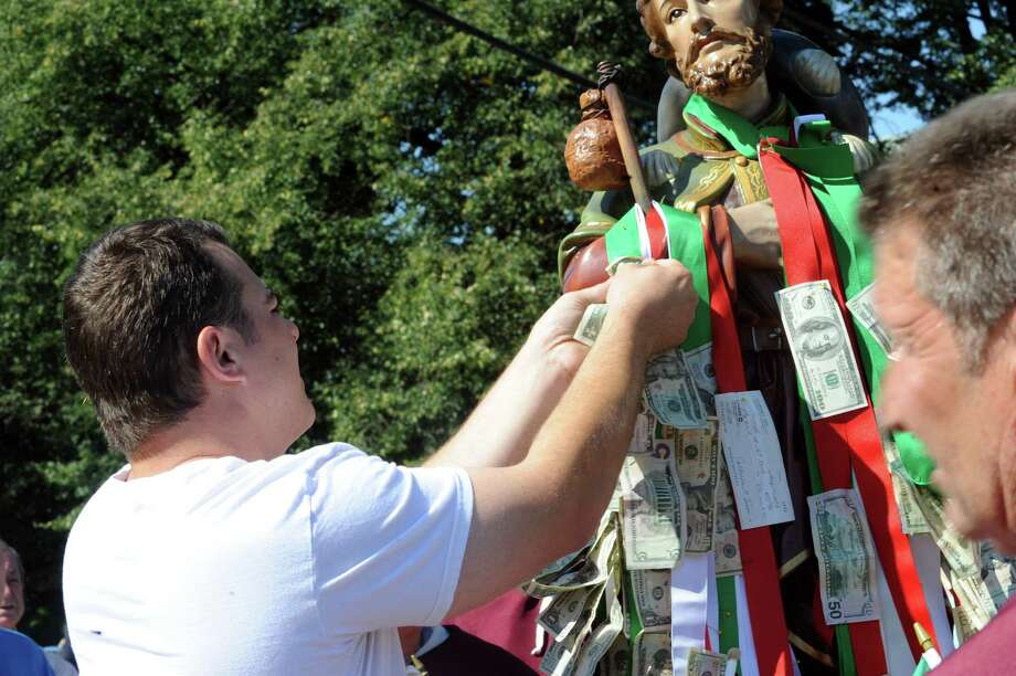 Michael Pitassi put money on the ribbon on Saint Roch on the float at the annual Saint Roch parade at Chickahominy, in Greenwich, Conn., Sunday, August 11, 2013. Photo: Helen Neafsey / Greenwich Time