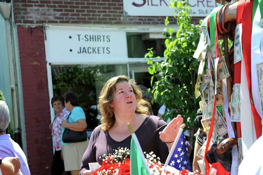 A woman looks at the money at the annual Saint Roch parade at Chickahominy, in Greenwich, Conn., Sunday, August 11, 2013. Photo: Helen Neafsey / Greenwich Time