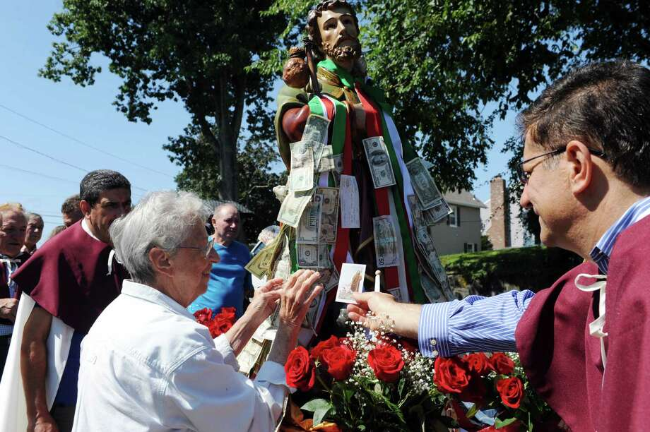 Joan Carlo puts money on the ribbons for Saint Roch at the annual Saint Roch parade at Chickahominy, in Greenwich, Conn., Sunday, August 11, 2013. Photo: Helen Neafsey / Greenwich Time