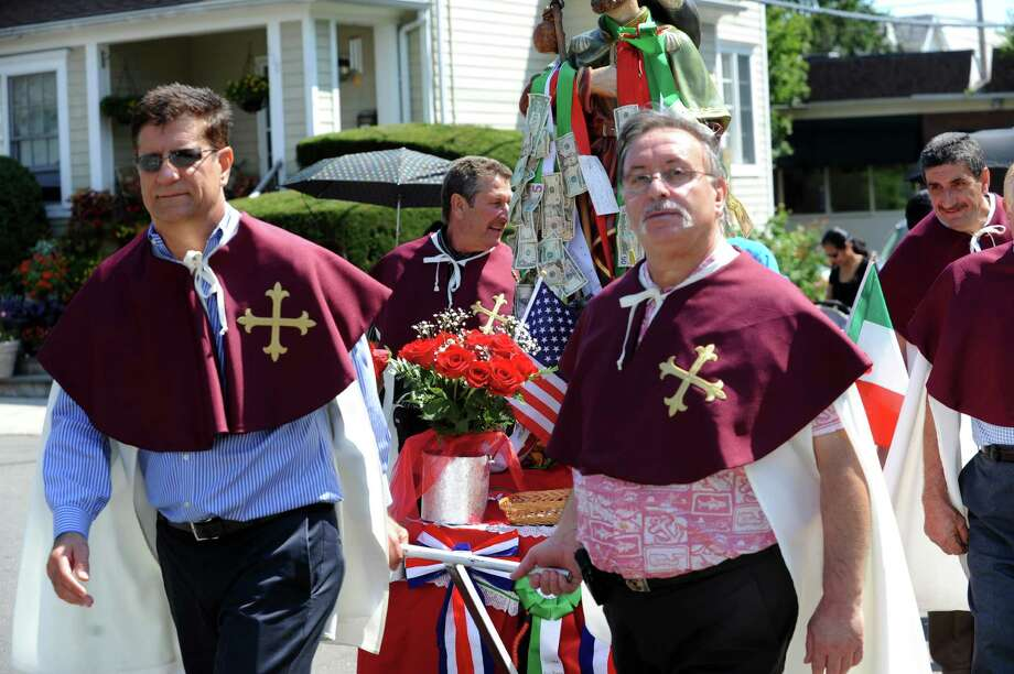 Angelo Mariani, of Harrison, left, and Giovanni Pennellle, of Greenwich, carries the float at the annual Saint Roch parade at Chickahominy, in Greenwich, Conn., Sunday, August 11, 2013. Photo: Helen Neafsey / Greenwich Time