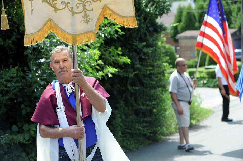 Rocco Pennella holds a flag at the annual Saint Roch parade at Chickahominy, in Greenwich, Conn., Sunday, August 11, 2013. Photo: Helen Neafsey / Greenwich Time