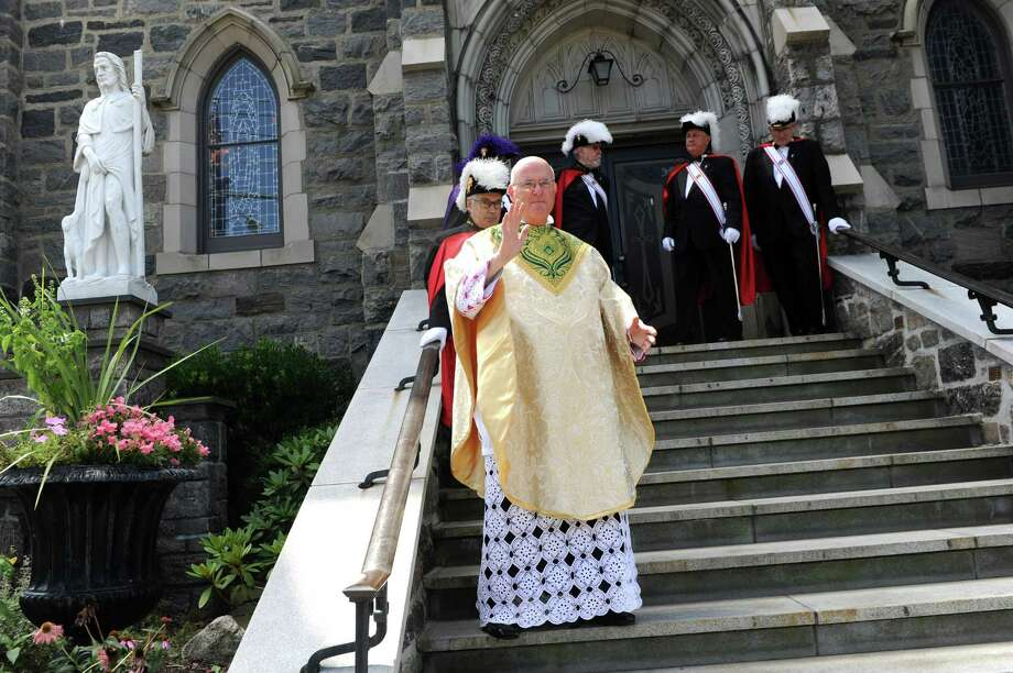 The Reverend Matthew Rocco Mauriello stands on the stairs of Saint Roch Church after parade at Chickahominy, in Greenwich, Conn., Sunday, August 11, 2013. Photo: Helen Neafsey / Greenwich Time