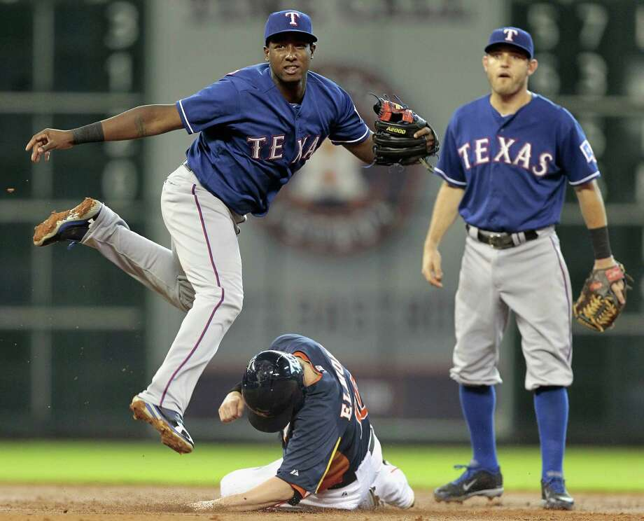 Jurickson Profar #13 of the Texas Rangers avoids the slide of Jake Elmore #10 of the Houston Astros as he throws to first base to complete a double play in the third inning at Minute Maid Park on August 11, 2013 in Houston. Photo: Bob Levey, Getty Images / 2013 Getty Images