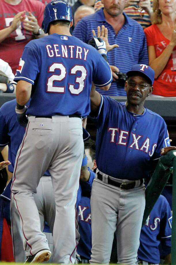 Texas Rangers manager Ron Washington, right, congratulates Craig Gentry (23) after he scored on a Jurickson Profar's single in the ninth inning of a baseball game against the Houston Astros, Sunday, Aug. 11, 2013, in Houston. The Rangers defeated the Astros 6-1. (AP Photo/Patric Schneider) Photo: Patric Schneider, Associated Press / FR170473 AP