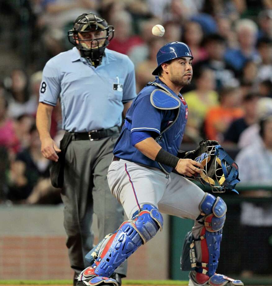 Catcher Geovany Soto #8 of the Texas Rangers can't locate the ball on a wild pitch in the third inning as home plate umpire Chris Guccione looks on against the Houston Astros at Minute Maid Park on August 11, 2013 in Houston. Photo: Bob Levey, Getty Images / 2013 Getty Images
