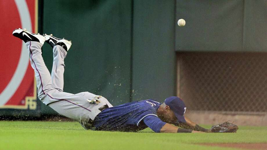 Alex Rios #51 of the Texas Rangers dives but comes up short on a line drive hit by Jose Altuve #27 of the Houston Astros in the first inning at Minute Maid Park on August 11, 2013 in Houston. Photo: Bob Levey, Getty Images / 2013 Getty Images