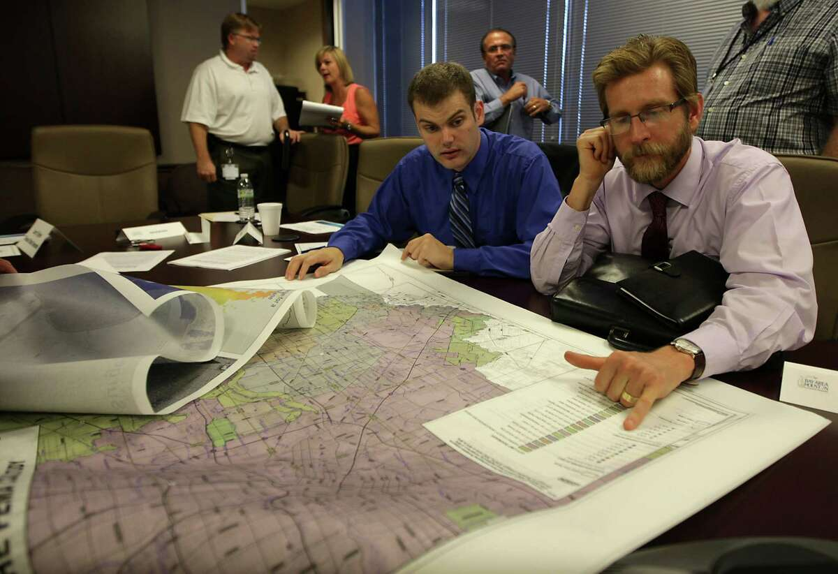 Stephen Cotten, left, and Jason Murasko, both University of Houston-Clear Lake assistant professors of economics, focus on new federal flood maps that put more homes into the flood plain at a meeting of coastal officials this month.