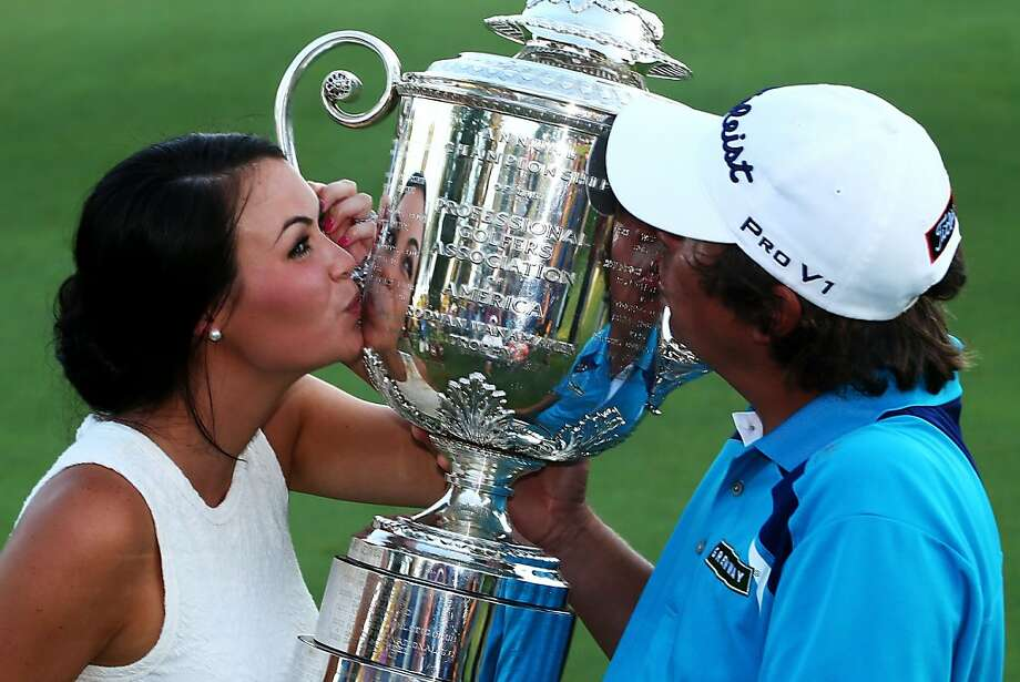 Jason Dufner and his wife, Amanda, kiss the PGA's Wanamaker Trophy on the 18th green after his first major championship victory. Photo: Streeter Lecka, Getty Images