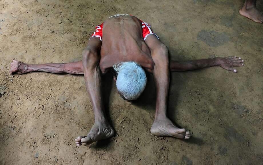 Human pretzel:Elderly Indian wrestler Ram Gopal is so flexible, he could probably fit in a carry-on bag. (Allahabad, India.) Photo: Sanjay Kanojia, AFP/Getty Images