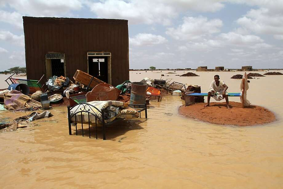 Instant lake in the desert:A Sudanese man takes refuge on a patch of higher ground as floodwater surrounds his   home on the outskirts of Khartoum. Drainage is notoriously poor in the capital, where   even small rainstorm can cause flooding. Photo: Ashraf Shazly, AFP/Getty Images