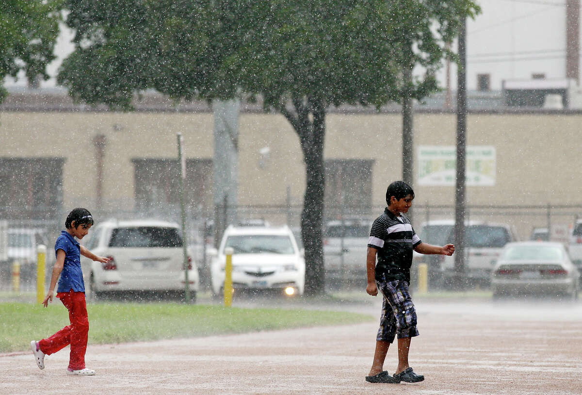 Children play in the rain while attending the Eid ul Fitr Festival held Sunday Aug. 11, 2013 at the San Antonio Museum of Art.