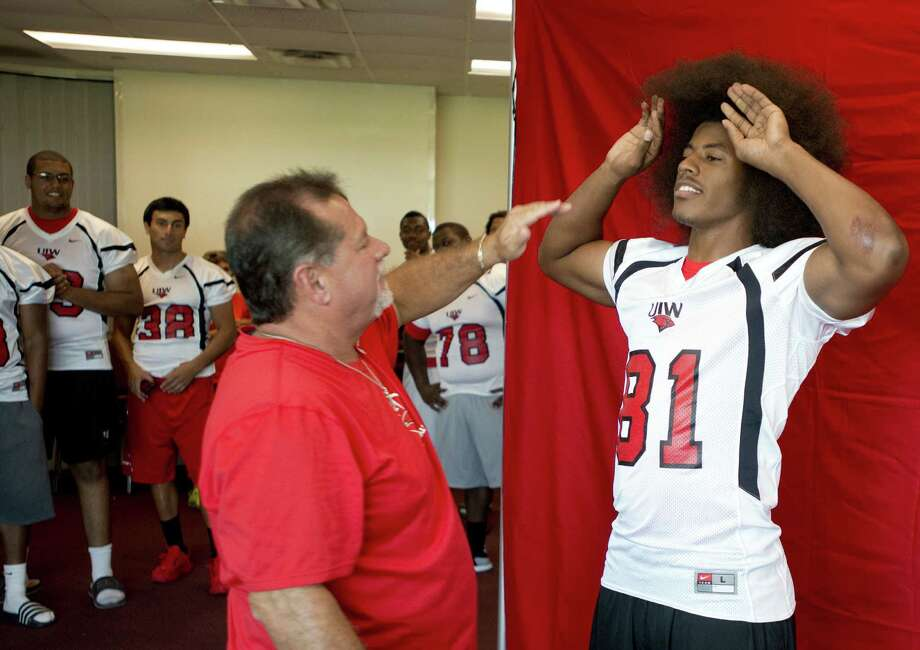 Tight end Trey Anderson (right) gets some help taming his hair from photographer Mark Walton for UIW's team picture Sunday at Benson Stadium. Photo: Darren Abate / For The Express-News