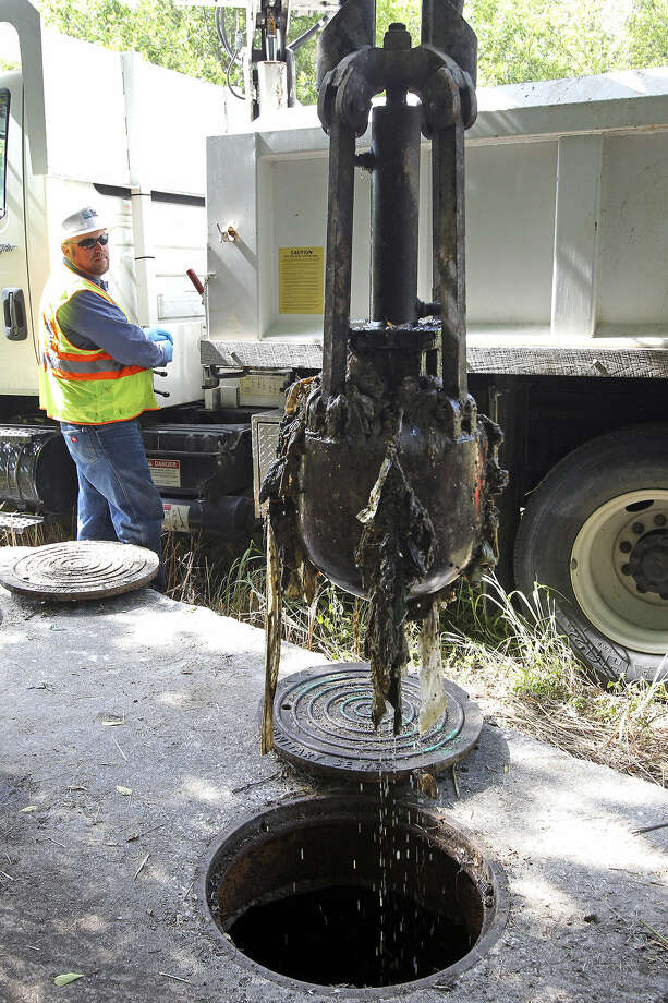 Aaron Loney operates a claw mechanism as he and a SAWS maintenance crew clean a clogged siphon system near Eisenhauer Road and Corinne Drive. Photo: Tom Reel / San Antonio Express-News