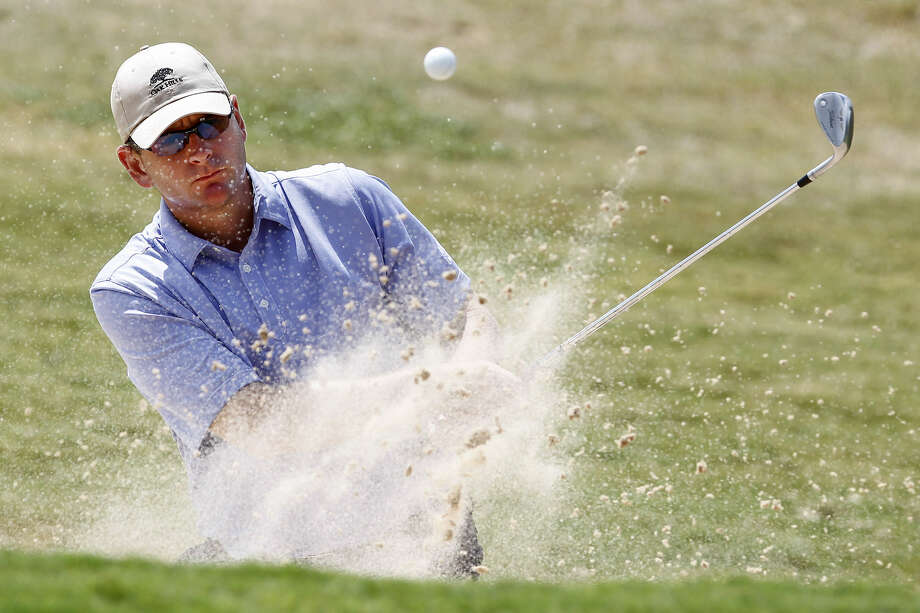 Danny Simmerman hits out of a bunker guarding the third green during the final round of the Greater S.A. men's match play championship. He beat Ian Evans 7 and 5 to win the tournament. Photo: Marvin Pfeiffer / San Antonio Express-News