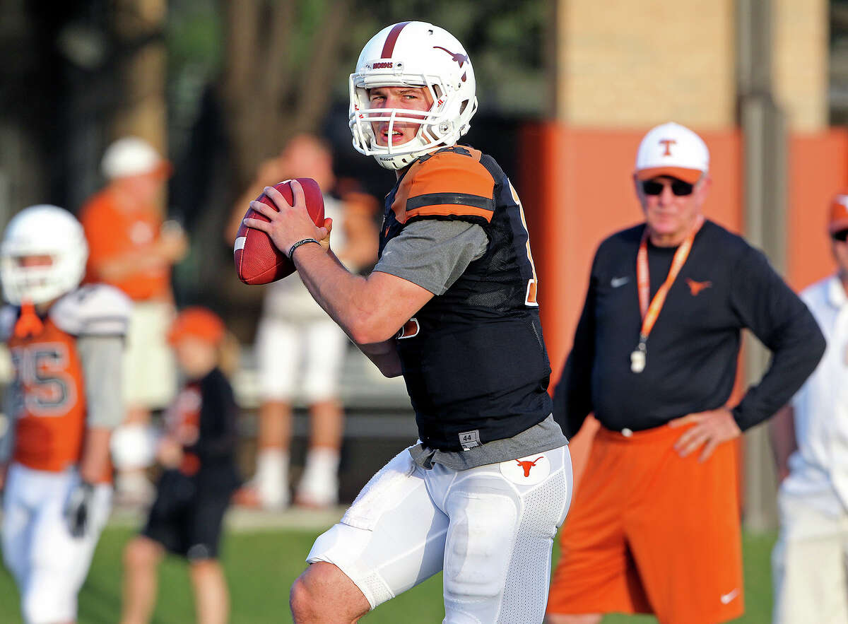 David Ash throws passes under watch by Mack Brown during UT football practice at Denius Fields in Austin on August 9, 2013.
