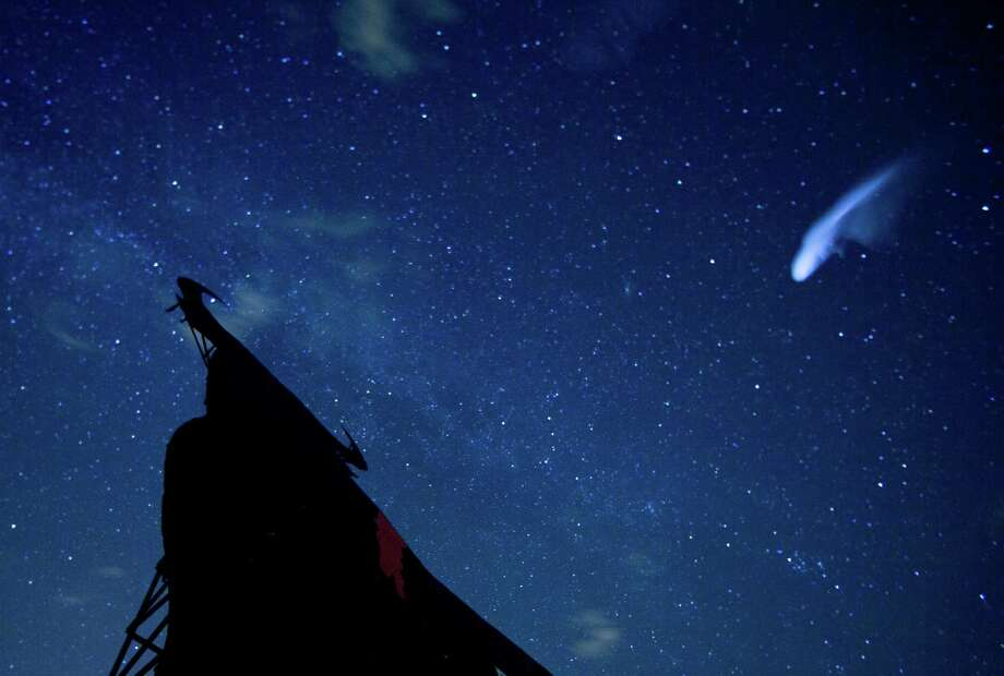 In this long exposure photo, a streak appears in the sky during the annual Perseid meteor shower above a roadside silhouette of a Spanish fighting bull, conceived decades ago in Spain as highway billboards, in Villarejo de Salvanes, central Spain in the early hours of Monday Aug. 12, 2013. (AP Photo/Paul White) Photo: Paul White, Associated Press / AP